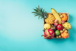 Tropical fruits on blue background. Rattan box full of exotic thailand fruits - pineapple, pitahaya, kiwano, african horned melon, tamarillo fruit, granadilla, feijoa, salak, snake fruits, maracuya
