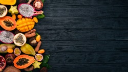 Tropical fruits, papaya, Dragon Fruit, rambutan, tamarind, cactus fruit, avocado, granadilla, carambola, kumquat, mango, mangosteen, passionfruit, coconut. On a wooden background.