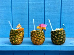 Tropical Fruity Pineapple Drinks with Umbrellas on Colorful Backgrounds