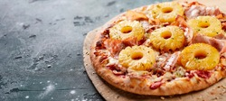 Tropical Hawaiian pizza with pineapple slices and ham on an oven-fired pastry base served whole on a board in a panorama banner with copyspace