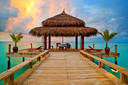 Tropical hut on water at sunset - romantic dinner in paradise