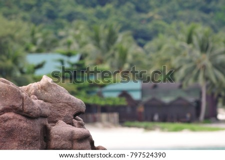 Tropical island beach stone bokeh background of palm tree and backpacker chalets resorts. A perfect image top copy space for hotel, resort, booking advert.   #797524390