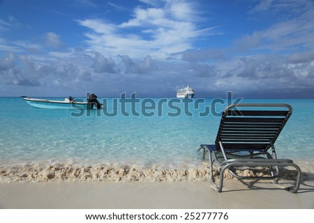 Tropical island beach with lounge chair, cruise boat and fishing boat