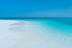 Tropical island in the Indian Ocean. White sand beach, blue sky and a strip of ocean