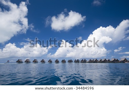 Tropical island resort on crystal clear water. - stock photo