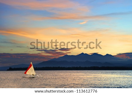 Tropical island sunset with sailing boat