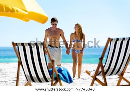 tropical island vacation summer beach couple walking holding hands and laughing together in the sun