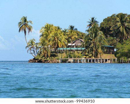 Tropical island with coconut trees and a dock leading to a small village, Caribbean sea, Archipelago of Bocas del Toro, Panama