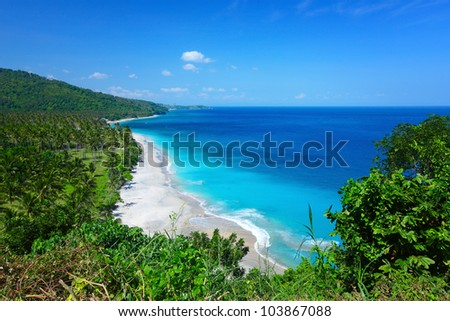 Tropical lagoon with clear water and beach with white sand and palm trees in a valley. Lombok island, Indonesia