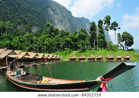 Tropical lakeside hut and wooden boat in ratchaprapa Dam,Khao Sok,Thailand - stock photo