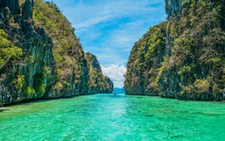 Tropical landscape - cristal clear water, rock islands, lonely boat