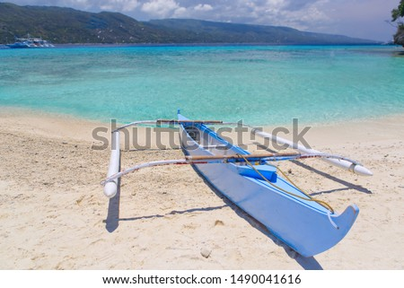 Tropical landscape with  Filipino traditional banka fishing outrigger boat on a white sand beach, beautiful clear turquoise water. Sumilon island, Philippines. Stok fotoğraf ©