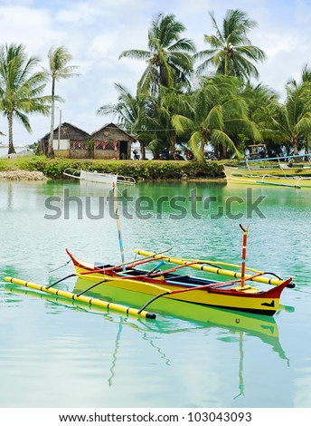 Tropical landscape with traditional Philippines boats and village on Calicoan island, Philippines