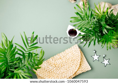 Tropical leaves and Beach bag with sunglasses  on  green  background. Top view, flat lay. #1060047593
