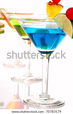 Tropical Martini Cocktails drink blue green and red on top composition with vodka, light rum, gin, tequila, blue curacao, lime juice in classic cocktail glasses isolated on a white background