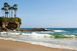 Tropical Ocean Paradise. Waves roll gently onto the beach at Crescent Bay Beach with cliffs, palm trees and yellow wildflowers in the distance on a beautiful sunny day in famed Laguna Beach, CA, USA.