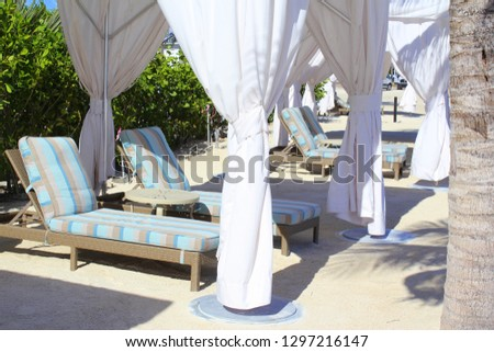 Tropical outdoor white tented room on the beach with long white curtains shading classic lounge chairs with muted blue, cream and taupe stripes in Islamorada in the Florida Keys during Christmas time. #1297216147
