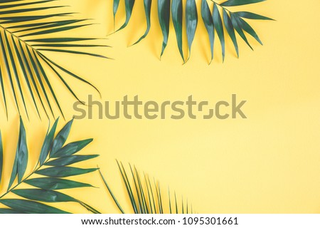 Tropical palm leaves on yellow background. Summer concept. Flat lay, top view, copy space #1095301661