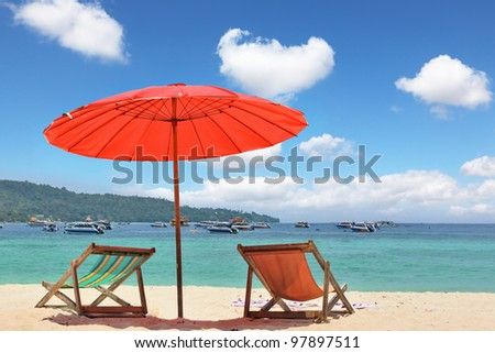 Tropical paradise on the shores of the azure sea. Red beach umbrella and deck chairs on the white sand