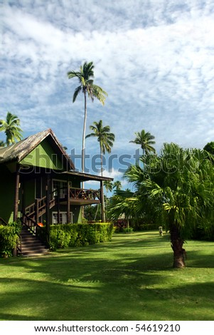 Tropical resort with green lawn and palm trees
