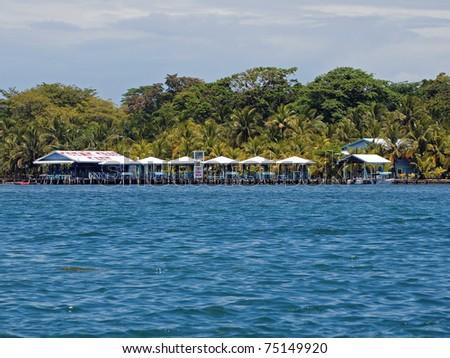 Tropical restaurant bar with kiosk over the sea and lush vegetation behind, Caribbean, Bocas del Toro, Panama