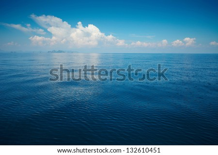 Tropical rippled and calm sea with far islands on the horizon and white fluffy clouds