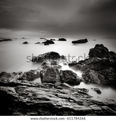 Tropical rocky beach at sunrise in black and white, A slow shutter speed was used to see the movement of the clouds in the sky.