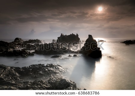 Tropical rocky beach at sunrise , located at Terengganu Malaysia.( long exposure photography,Soft focus due to long exposure shot. Nature composition )