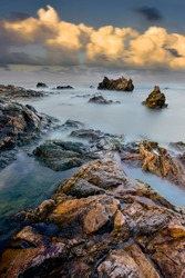 Tropical rocky beach at sunrise ( long exposure photography), Soft effect due to long exposure shot.