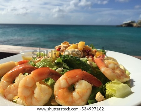 Shutterstock Tropical salad with shrimps and papaya. Caribbean food. Caribbean salad. Summer food. Seafood platter. Caribbean cuisine. Delicious healthy food. Food background. Caribbean background. Seafood salad.
