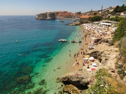 Tropical sandy beach with tourists and emerald/turqoise colored sea on a sunny summer day near the ancient and walled city of Dubrovnik, Croatia
