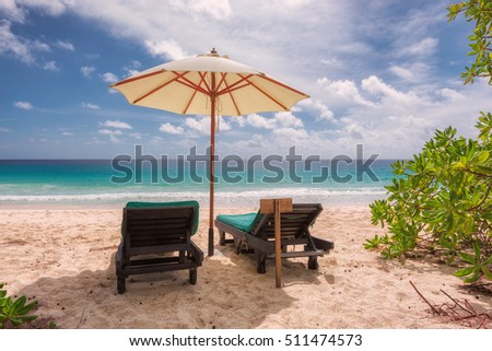 Tropical sandy beach with umbrella and beach chair #511474573