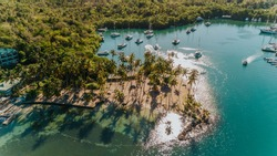 Tropical sandy island with palm trees in a blue lagoon, exotic bay in the Caribbean island, sailboats anchoring in a bay, yachting lifestyle in Marigot Bay of St Lucia