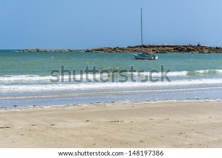 tropical scene with beautiful beach, blue water, and a sailboat