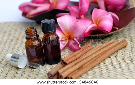 tropical spa concept with some cinnamon,plumeria flowers and liqiud bottle