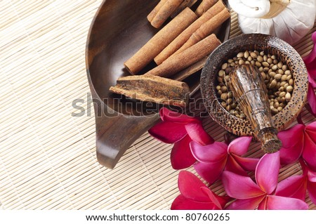 tropical spa concept with some cinnamon,plumeria flowers, liquid bottle and aroma item