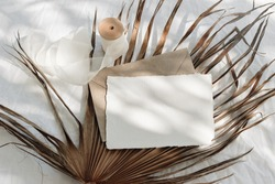 Tropical stationery still life. Closeup of blank card mock-up and craft envelope in sunlight. Dry palm leaf , white linen table cloth background. Summer vacation concept. Boho design. Flat lay, top.