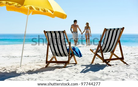 Tropical summer beach holiday couple walk towards the ocean holding hands while on honeymoon vacation #97744277