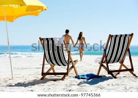 Tropical summer beach holiday couple walk towards the ocean holding hands while on honeymoon vacation #97745366