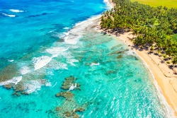 Tropical summer beach with coconut palm trees background. Aerial drone idyllic turquoise sea vacation background. Dominican Republic