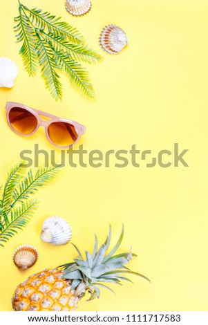 Tropical summer concept with woman fashion accessories, leaves and pineapple on yellow background. Flat lay, top view #1111717583