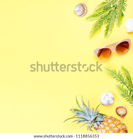 Tropical summer concept with woman fashion accessories, leaves and pineapple on yellow background. Flat lay, top view #1118856353