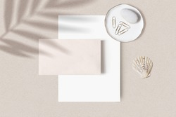 Tropical summer stationery mock-up scene. Blank business card, porcelain plate with stone, gold paper clips and sea shell, beige textured table background. Palm leaf shadow overlay. Flat lay, top view