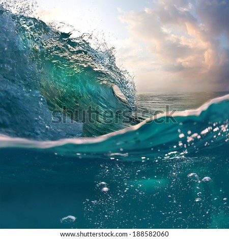 Tropical sunset background. Beautiful colorful ocean wave breaking closing near sand beach