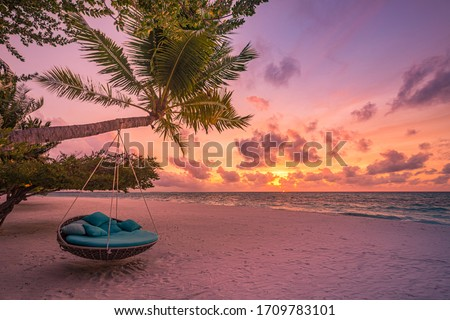 Tropical sunset beach and sky background as exotic summer landscape with beach swing or hammock and white sand and calm sea beach banner. Paradise island beach vacation or summer holiday destination