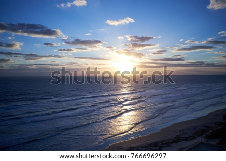 Tropical sunset over a tranquil beach in Florida, USA with the setting sun casting a glowing path across the coean #766696297