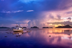 Tropical sunset with a banca boat in El Nido, Palawan - Philippines.