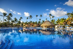 Tropical swimming pool and palm trees in luxury resort