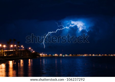 Tropical thunderstorm at night over Miami with massive lightning bolt