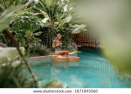Tropical travel lifestyle, vacation on Bali island. Pretty young woman enjoying breakfast in the swimming  pool diring tropical vacation Photo stock ©